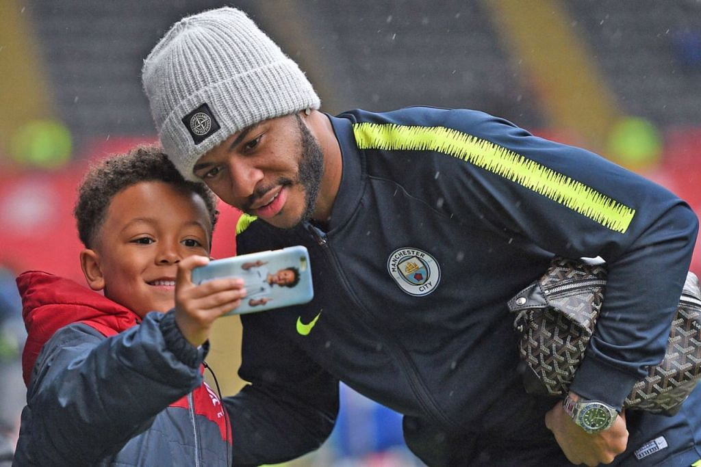 BERGAMBAR DENGAN PEMINAT: Raheem Sterling (kanan) yang sempat menggembirakan seorang peminat cilik, tidak begitu menghiraukan kritikan daripada pihak media dan mahu menumpukan perhatiannya kepada kerjayanya sebagai pemain bola sepak. - Foto AFP
