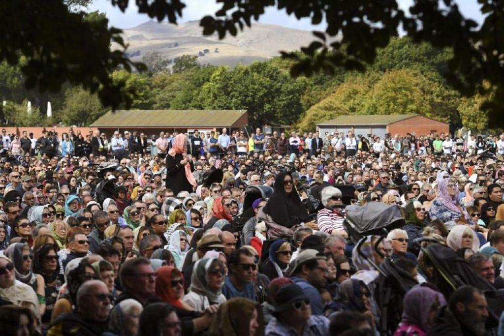 Orang ramai berdiri semasa perhimpunan bagi solat Jumaat berjemaah dan tafakur dua minit bagi mangsa pembunuhan beramai-ramai di dua masjid, di Hagley Park di Christchurch hari ini (22 Mac).