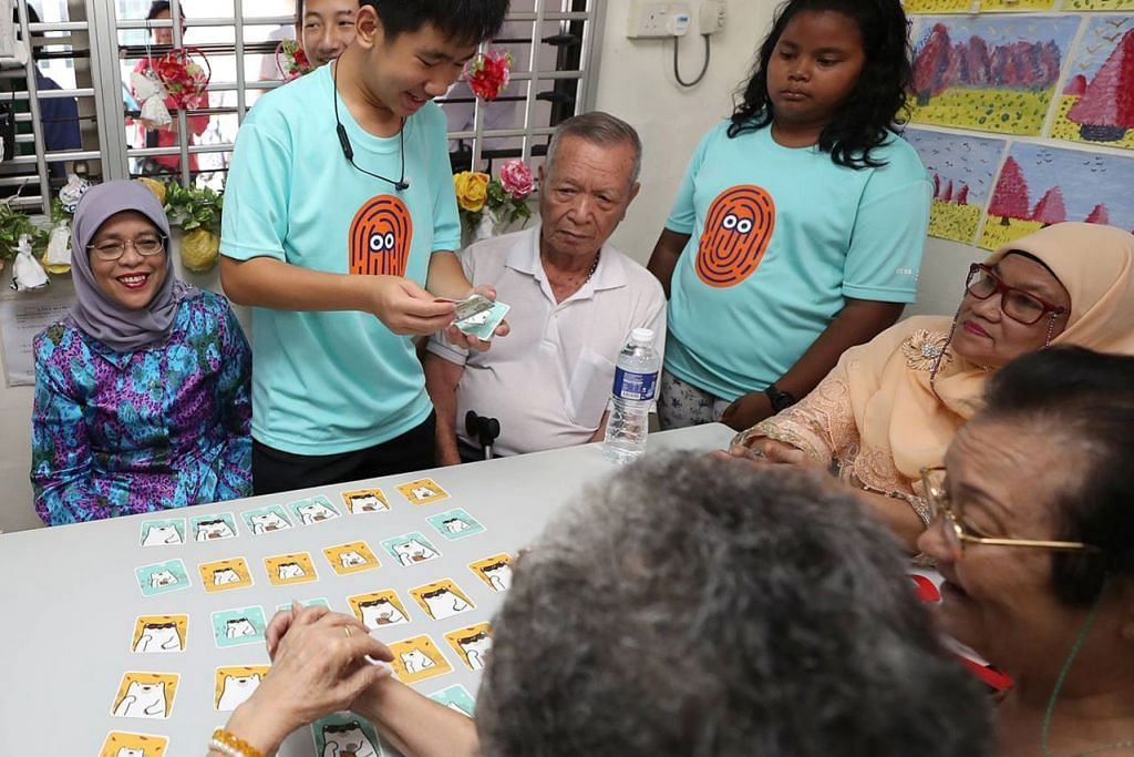 LAWAT WARGA EMAS: Puan Halimah (kiri) bermain 'Pick a Seal' dengan sekumpulan warga tua di Pusat Kegiatan Warga Emas CareElderly, Merpati Road, semalam. Menerusi Facebook semalam, beliau rasa gembira melihat wajah girang di sekeliling sedang mereka membina ikatan antara generasi. – Foto MCI