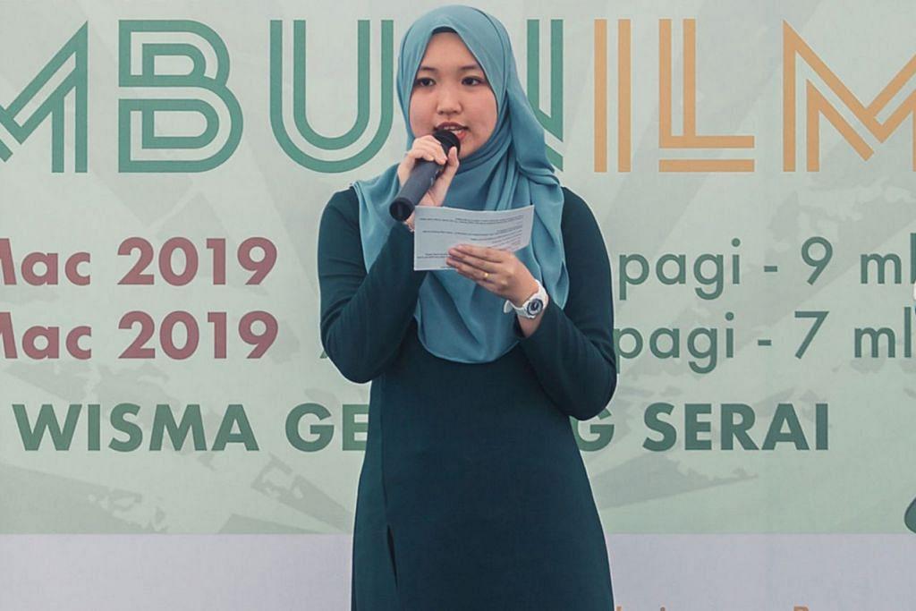 LUAHKAN KISAH CERPEN: Cik Nurain Mohd Zulkepli memberi sedikit cebisan cerpen tulisannya kepada hadirin semasa majlis pelancaran buku di Pesta Buku Melayu Singapura baru-baru ini.