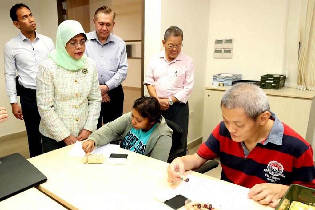 DEKATI MASYARAKAT: Presiden Halimah melawat golongan kurang upaya dan meninjau kegiatan mereka di Rumah Golongan Dewasa Kurang Upaya Thye Hua Kwan semalam. - Foto MCI
