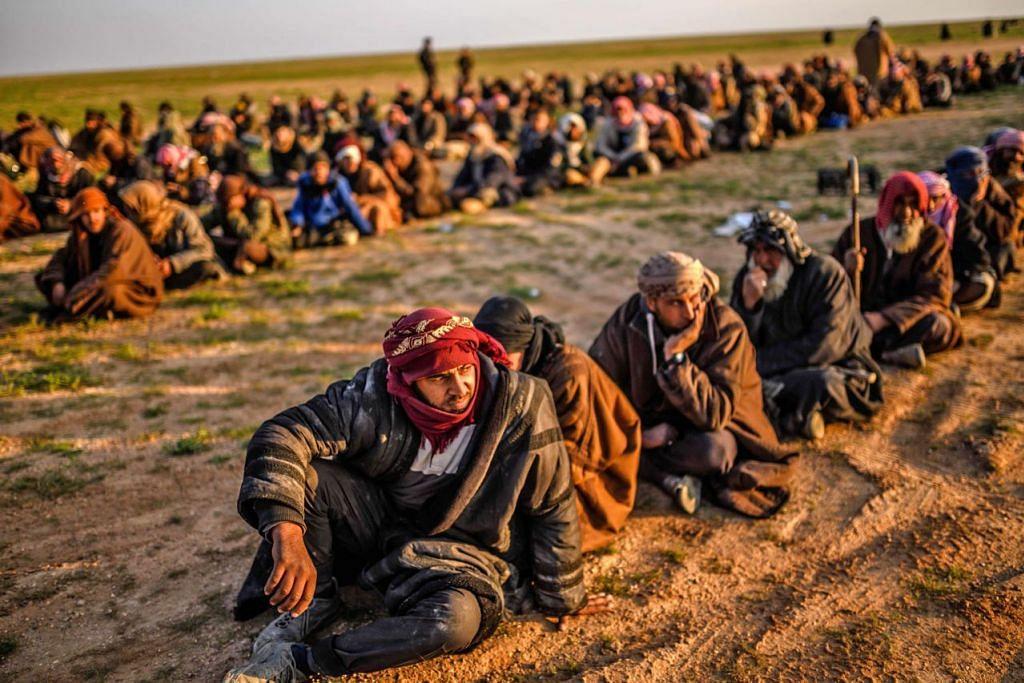 MENANTI DIPERIKSA: Suspek pejuang ISIS menanti disaring oleh anggota SDF selepas mereka meninggalkan kubu terakhir kumpulan itu di Baghouz bulan lalu. - Foto AFP