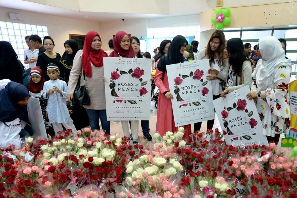 BALAS KEBENCIAN DENGAN KEAMANAN: Sukarelawan gerakan memupuk keamanan dan keharmonian antara kaum dan agama, Roses of Peace (ROP), mengadakan pengagihan bunga mawar sebagai tanda keamanan. - Foto fail