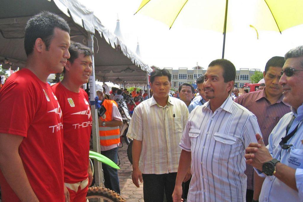 SUKAN LASAK: Gambar atas pula menunjukkan Amin dan rakan sepasukan, Kwok Wing Kit (kededuanya berpakaian merah), berbual dengan Agong Malaysia ketika itu, Sultan Mizan Zainal Abidin, sebelum perlumbaan FIM Asia 2011. - Foto ihsan MUHAMMAD AMIN KHALID