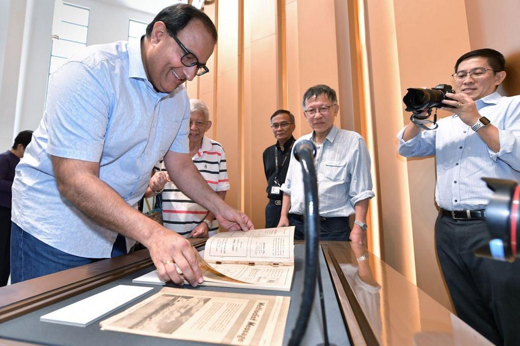 LIHAT KOLEKSI LAMA: Encik S Iswaran (kiri) membelek buku yang merupakan antara bahan bersejarah yang dipamerkan di bangunan Arkib Nasional Singapura (NAS) yang dibuka semula kepada orang ramai semalam. - Foto BH oleh NG SOR LUAN