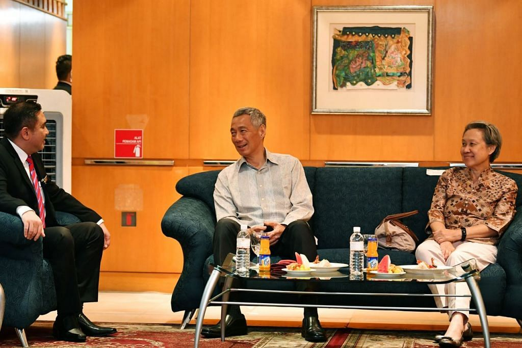 PERERAT HUBUNGAN: Encik Lee Hsien Loong (tengah) dan isterinya, CIk Lee disambut oleh Encik Anthony Loke (kiri) di Lapangan Terbang Antarabangsa Kuala Lumpur (KLIA) semalam. - Foto BH oleh LIM YAOHUI