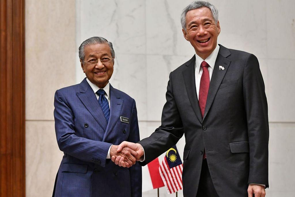 CARI HURAIAN BERSAMA: Encik Lee (kanan) berjabat tangan dengan Dr Mahathir selepas menandatangani buku tamu di Bangunan Perdana Putra sebelum pertemuan empat mata semalam. - Foto BH oleh LIM YAOHUI
