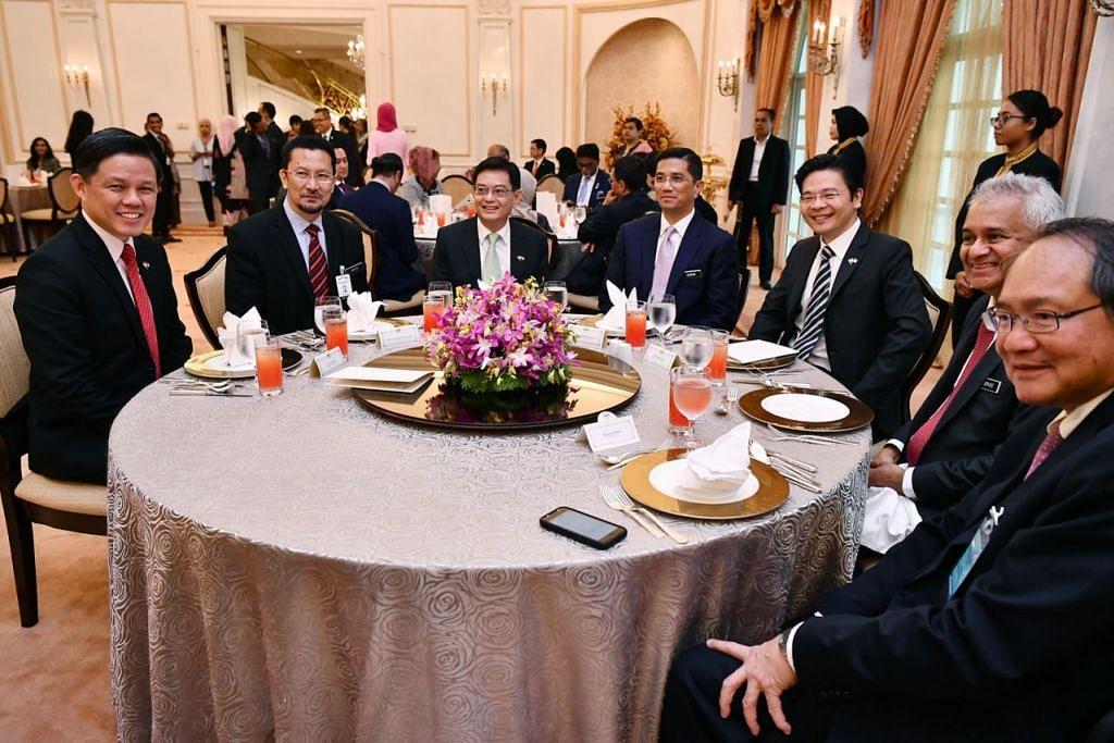 MAKAN BERSAMA: Sekumpulan menteri Singapura dan Malaysia dengan beberapa pegawai kanan dua negara bergambar bersama di majlis makan tengah hari rasmi di Seri Perdana, Putrajaya. - Foto BH oleh LIM YAOHUI