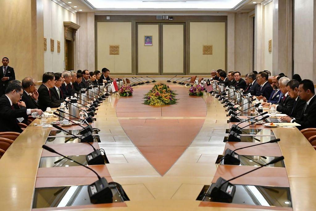 SEMANGAT MUHIBAH: PM Lee (kiri) serta sembilan menteri Kabinetnya mengadakan mesyuarat dengan Dr Mahathir (kanan) serta sembilan menteri beliau dalam Rahat Pemimpin yang diadakan di Putrajaya semalam. - Foto BH oleh LIM YAOHUI