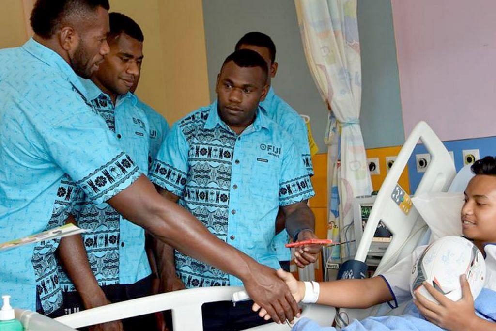 KONGSI KEGEMBIRAAN: Pemain Fiji 7s sempat beramah mesra dengan salah seorang pesakit kanak-kanak di KKH, Muhammad Syabil Muhammad Zaini. - Foto BH oleh FIJI AIRWAYS