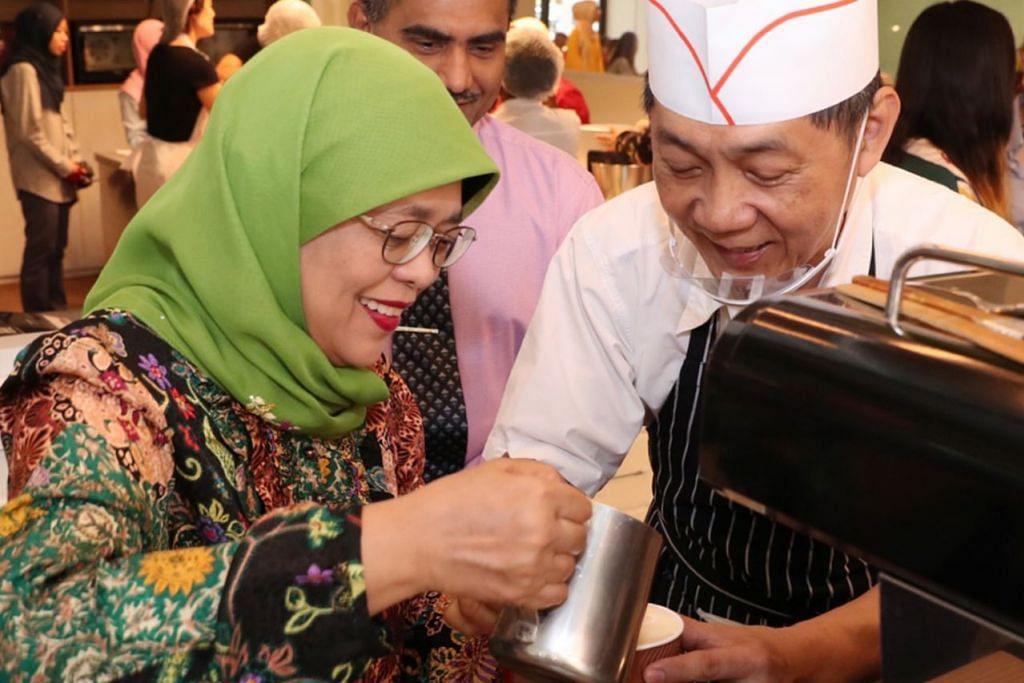 GEMBIRA BERINTERAKSI: Presiden Halimah Yacob sempat mempelajari cara membuat kopi daripada Encik Chua Kok Leong, seorang sukarelawan yang mengendalikan kafe 'Give n Take' di Pusat Aktiviti Sasco@Khatib. - Foto MCI