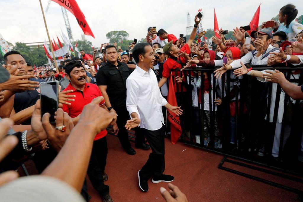 ANAK JATI DISAMBUT HANGAT: Encik Jokowi, berkemeja putih biasanya, disambut dengan hangat apabila pulang berkempen di Solo, tempat mula kerjaya politiknya sebagai Mayor hingga akhirnya menjadi Presiden pada 2014. Beliau berharap mendapat lebih daripada 84 peratus undi yang diraihnya dulu pada pilihan raya 17 April. - Foto REUTERS