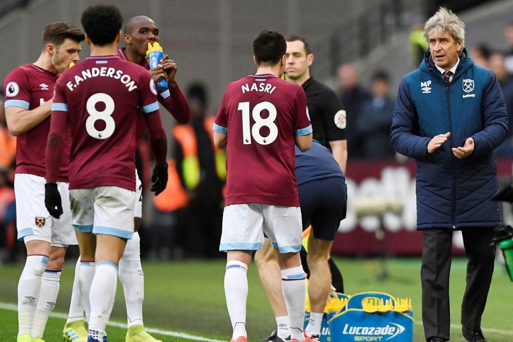 MEMBERI DORONGAN DAN PERANGSANG: Pengurus West Ham, Manuel Pellegrini (kanan), mendekati anak buahnya semasa mereka mengambil kesempatan melepaskan dahaga semasa pengadil menghentikan sementara perlawanan sewaktu menentang Huddersfield Town di Stadium London pada 16 Mac lalu di mana West Ham menang 4-3. - Foto REUTERS