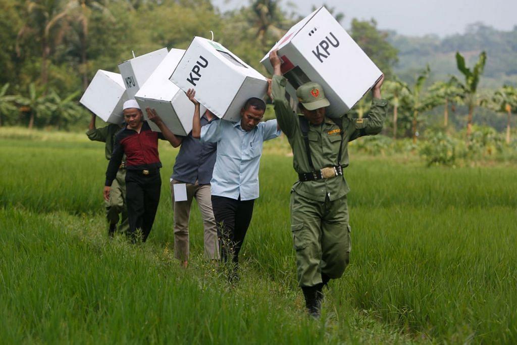 MERENTAS BENDANG: Para kakitangan pemerintah memikul peti undi untuk ditempatkan di kampung-kampung di Bogor, selatan Jakarta. - Foto EPA-EFE