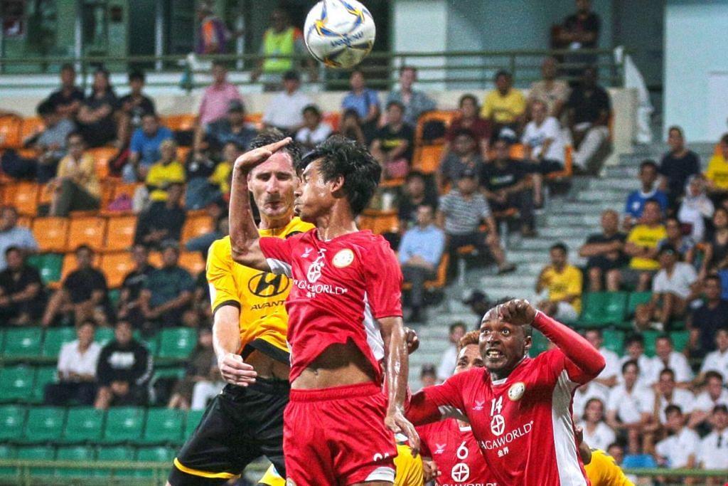PENUH DRAMA: Pemain Tampines Daniel Bennett (jersi kuning) dan pemain Nagaworld Leng Makara melompat tinggi untuk merebut bola dalam perlawanan di Stadium Jalan Besar. Tampines menjaringkan dua gol pada saat terakhir untuk memenangi perlawanan 4-2. - Foto BH oleh JASON QUAH