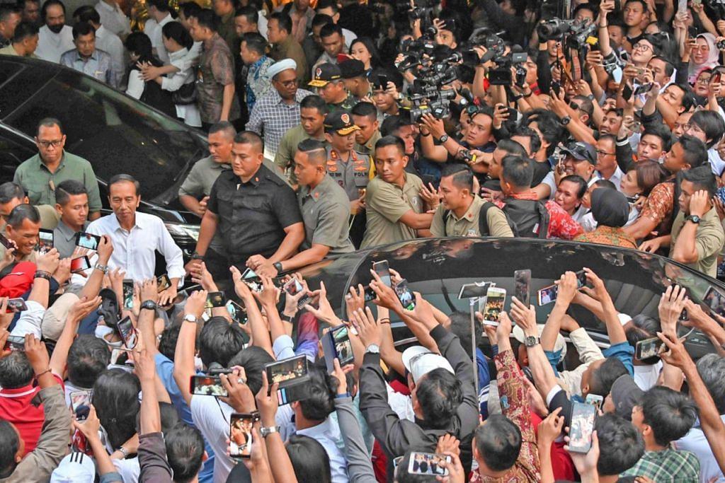 DIKERUMUN PENYOKONG: Presiden Joko Widodo (gambar atas, berbaju putih) dan calon Presiden Prabowo Subianto masing-masing dikerumun penyokong mereka semasa hari mengundi Pilihan Raya Presiden kelmarin. - Foto-foto AFP, REUTERS