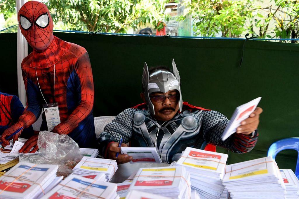 ADIWIRA JAGA PUSAT MENGUNDI: Pegawai pilihan raya yang berpakaian seperti adiwira seperti 'Spiderman' (kiri) dan Thor (kanan) menyiapkan kertas mengundi di Surabaya, Jawa Timur, kelmarin. - Foto REUTERS