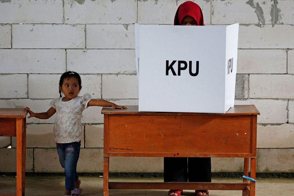 TUNGGU WALAU TIDAK DAPAT UNDI: Seorang budak perempuan sabar menanti di sebelah seorang pengundi di pusat mengundi di Bogor, Jawa Barat, kelmarin.