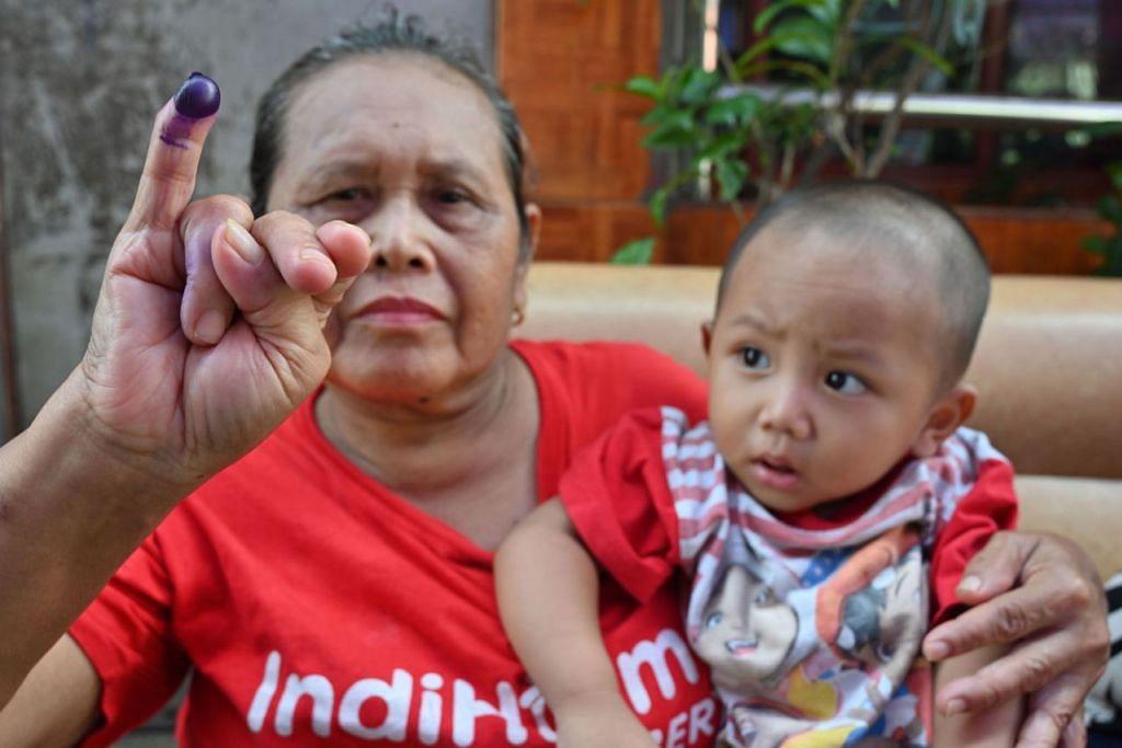 BUKTI SUDAH UNDI: Seorang penduduk setempat menunjukkan jarinya yang telah dicelup dakwat sebagai tanda beliau sudah membuang undi.