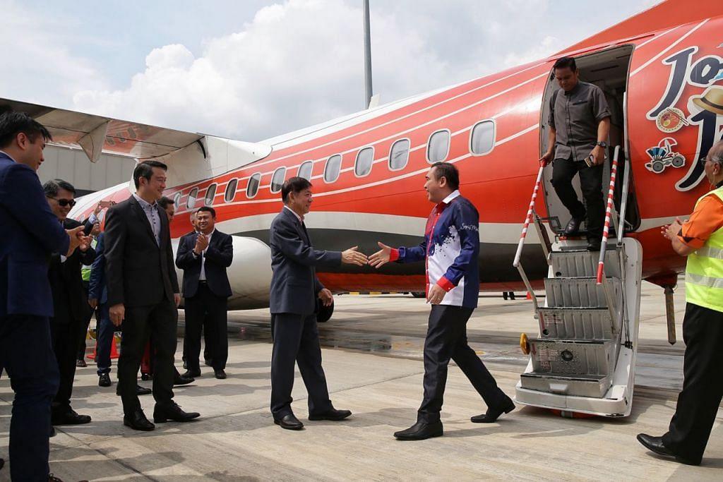 SAMBUT KETIBAAN: Menteri Pengangkutan Encik Khaw Boon Wan (kiri) menyambut ketibaan Menteri Pengangkutan Malaysia Encik Anthony Loke (kanan) yang tiba dari Subang menaiki pesawat Firefly. - Foto BH oleh KEVIN LIM.