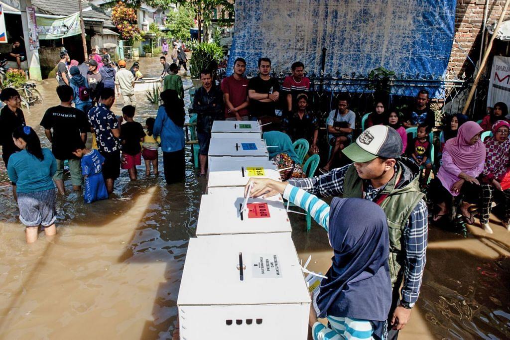 DEMI DEMOKRASI: Bah tidak menghalang rakyat Indonesia melaksana hak mereka di sebuah pusat mengundi Bandung. Di Surabaya, adi wira seperti Spiderman melicinkan pengundian. - Foto EPA-EFE