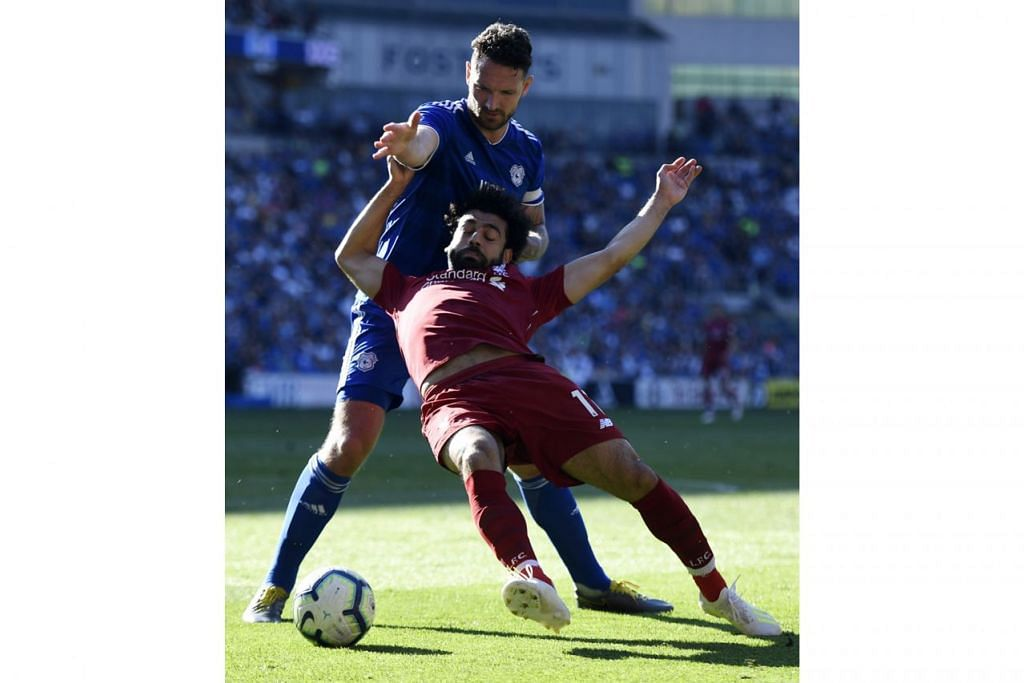DITARIK LAWAN: Mohamed Salah (berbaju merah) seolah-olah 'ditarik' kapten Cardiff City, Sean Morrison, sehingga menyebabkan pengadil memberikan tendangan penalti kepada Liverpool. - Foto EPA-EFE.