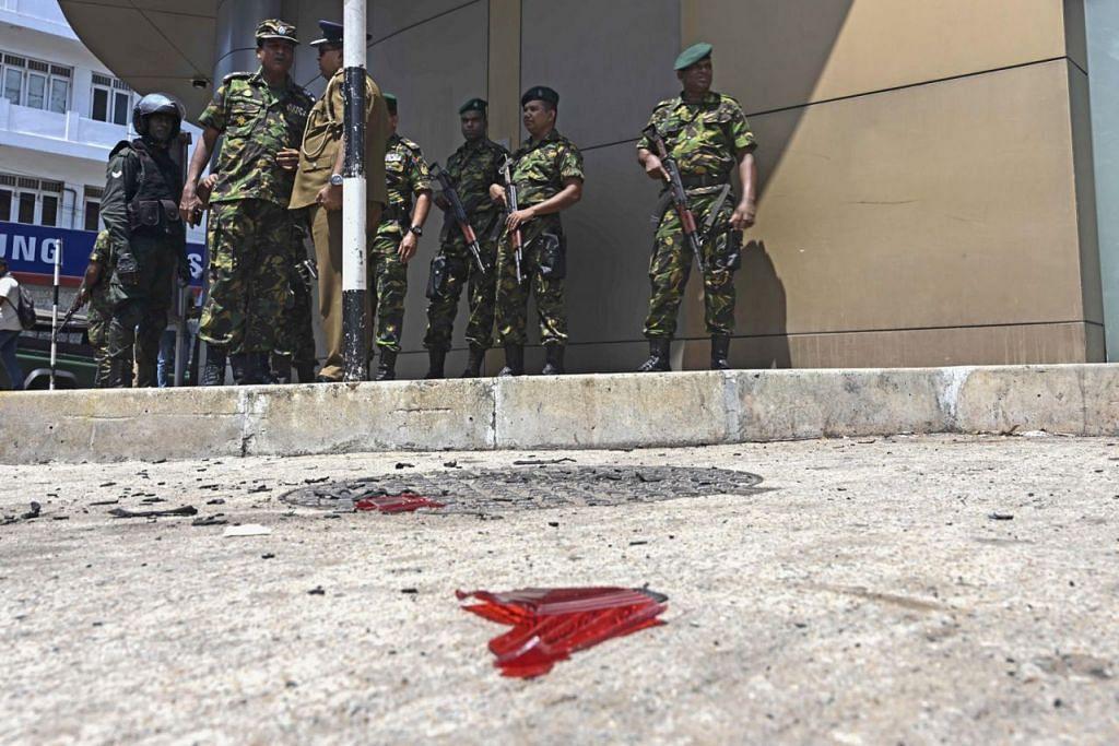 PERTINGKAT KESELAMATAN: Pegawai berdiri dekat serpihan motosikal di Colombo semalam.   - Foto AFP