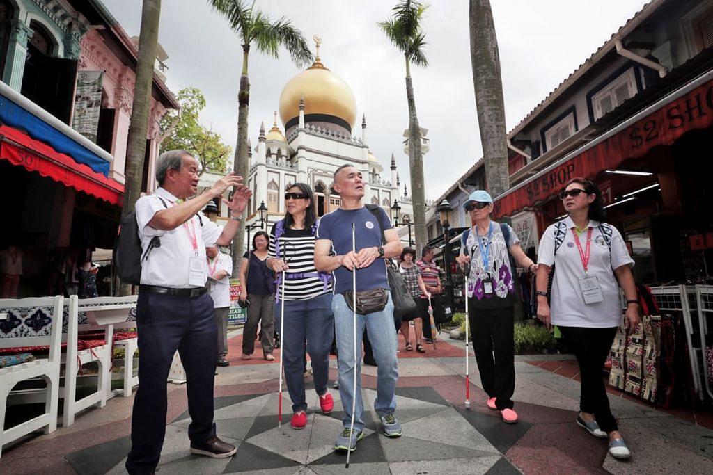 JALAN KENANGAN: Encik Chhua Bak Siang (kiri), 71 tahun, memimpin golongan cacat penglihatan dari Guide Dogs Singapore melawat sekitar Bussorah Street. - Foto BH oleh KELVIN CHNG