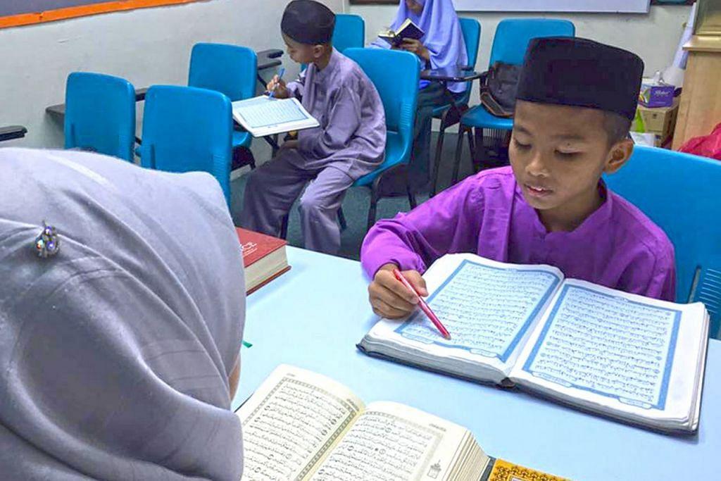 KLINIK RAMADAN: Peserta Klinik Ramadan (kanan) menyemak semula huruf 'Hijaiyah' bersama pembimbing klinik. – Foto PERDAUS