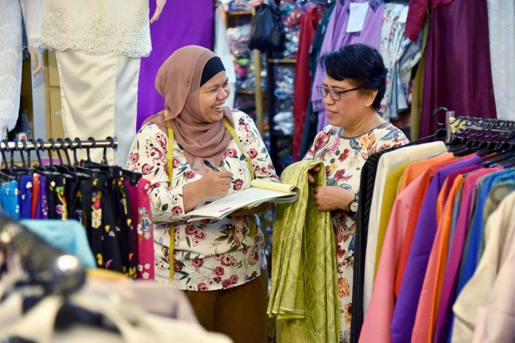 PELANGGAN SETIA: Cik Yate Ali, pemilik Adelea Boutique yang terletak di Joo Chiat Complex (kiri), sedang mengambil ukuran dan membincang stail rekaan bagi pelanggan tetapnya, Cik Rohana Ali, 61 tahun. – Foto BM oleh JASMINE CHOONG