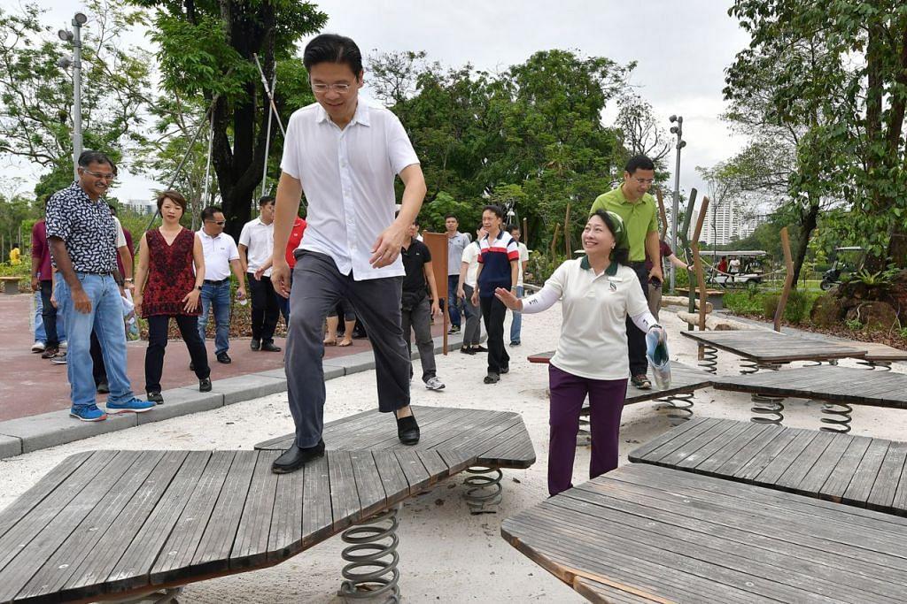 TAMAN BARU: Menteri Pembangunan Negara, Encik Lawrence Wong (depan) meninjau taman permainan, salah satu ciri menarik di Taman Lakeside. - Foto BM oleh NG SOR LUAN