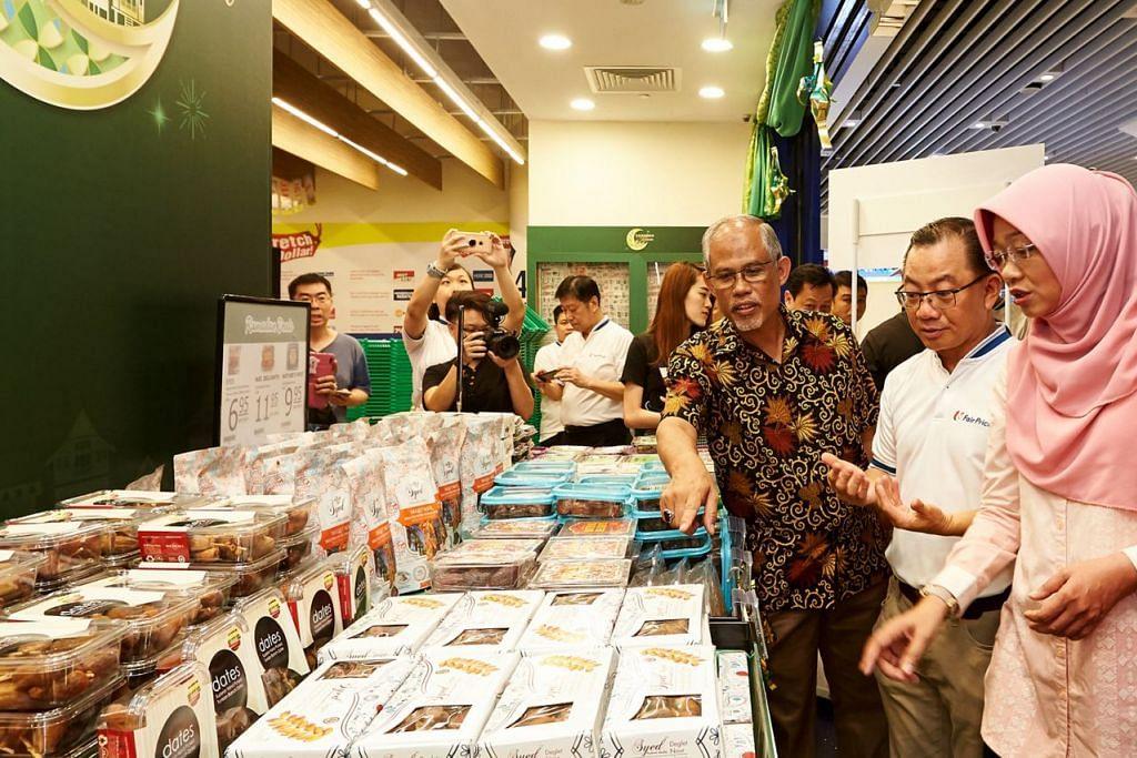 HARGAI SUMBANGAN: Encik Masagos (tiga dari kanan) berasa kagum dengan pelbagai jenis kurma yang kini dijual di NTUC FairPrice sambil disaksikan Encik Seah (dua dari kanan) dan Cik Rahayu (kanan). - Foto BH oleh ROSLEE ABDUL RAZAK