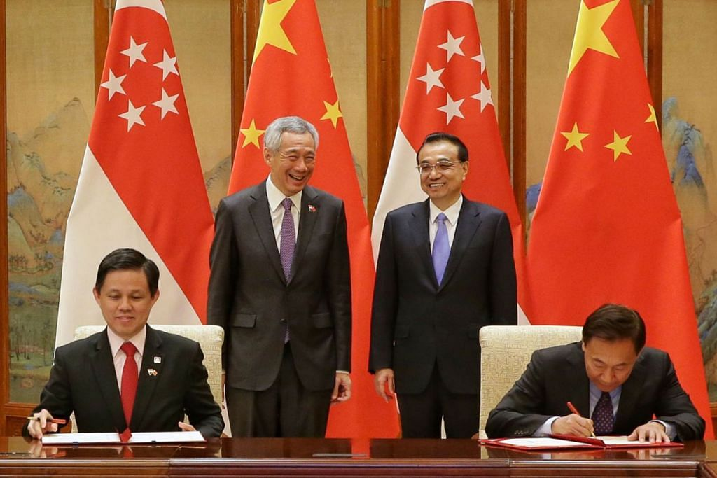 PERJANJIAN KERJASAMA: Encik Lee (berdiri, kiri) dan rakan sejawatan dari China Encik Li (berdiri, kanan) memerhatikan rakan senegara masing-masing menandatangani memorandum persefahaman (MOU) di Diaoyutai semalam. Mewakili Singapura ialah (duduk, kiri) Menteri Perdagangan dan Perusahaan Encik Chan Chun Sing (duduk, kiri) dan naib pengerusi Suruhanjaya Pembangunan dan Pemulihan Kebangsaan China, Encik Zhang Yong. - Foto BH oleh KEVIN LIM