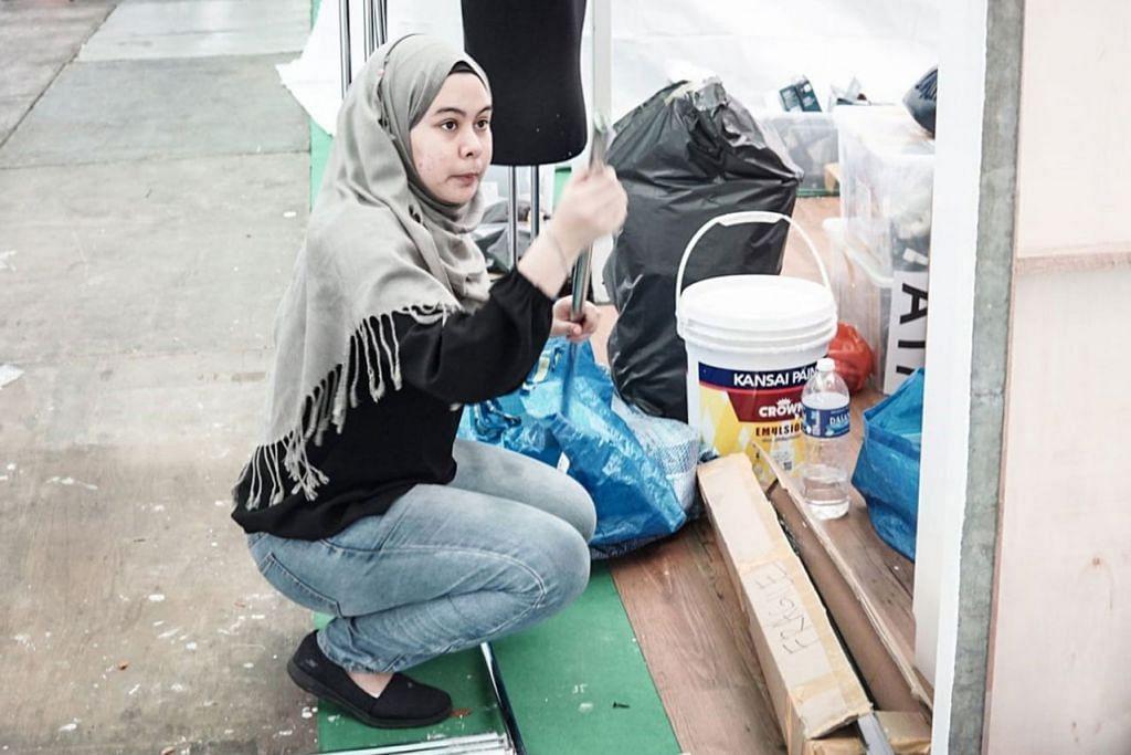 KEMAS SEKITARAN AGAR RAPI: Seorang pengendali gerai mengemas kawasan gerai untuk pembukaan Bazar Raya di Geylang Serai. - Foto BH oleh NUR DIYANAH TAHA