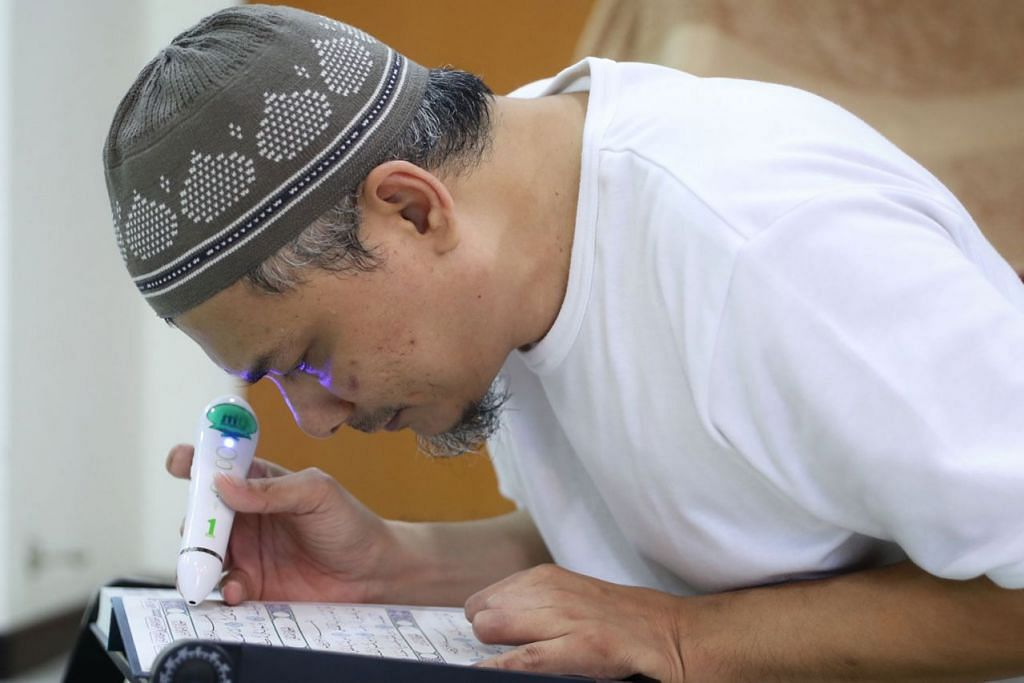 TERUS MENGAJI: Selepas penglihatannya kembali sekitar 30 peratus, Encik Mohamad Hasri memastikan beliau mengambil peluang tersebut untuk membaca Al-Quran. - Foto BH oleh GAVIN FOO