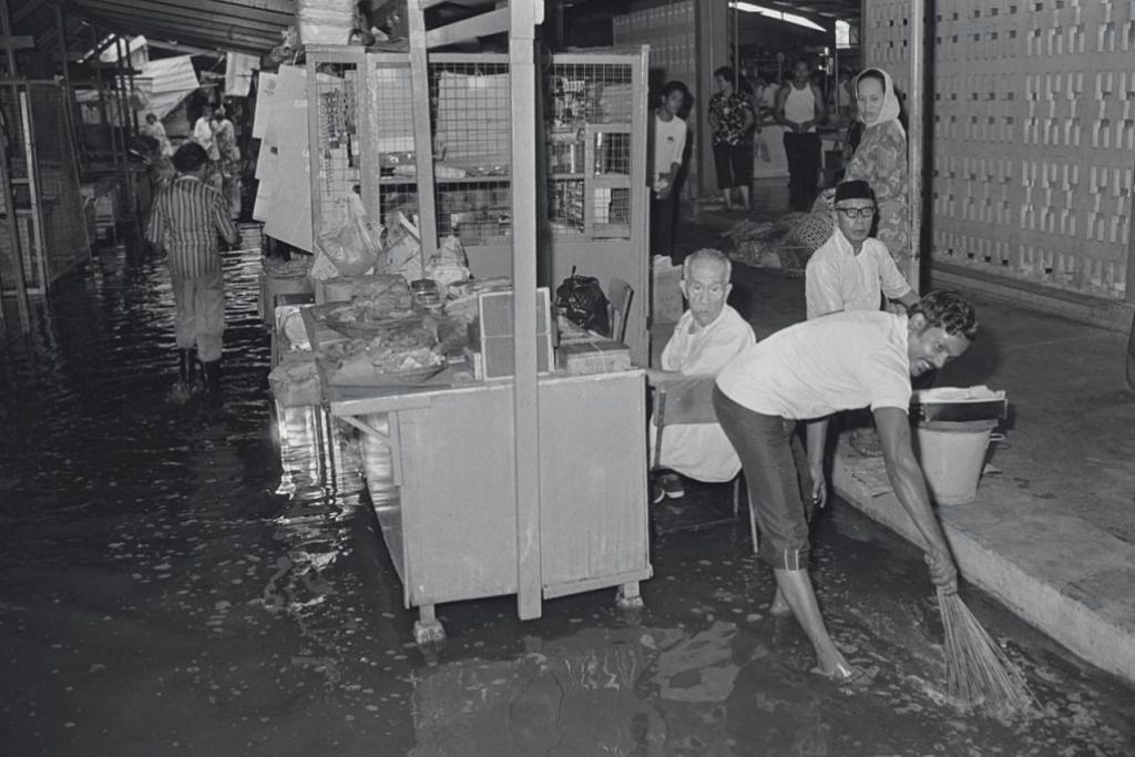 BANJIR: Seorang pegerai pasar Geylang Serai membersihkan kawasan yang terjejas akibat banjir. Pasar Geylang Serai, (yang kini telah dirobohkan dan digantikan dengan kemudahan baru) secara tradisi merupakan pusat popular bagi masyarakat Melayu/Islam khususnya semasa bulan Ramadan. Foto diambil pada 1980.