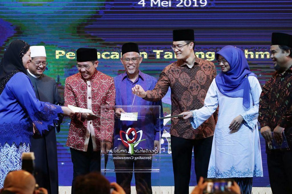 DERMA SIMBOLIK: (Dari kiri) Pengerusi Mesra, Cik Amatul Jameel Suhani Sujari; Mufti, Dr Mohamed Fatris Bakaram; Menteri Negara Kanan (Pertahanan merangkap Ehwal Luar), Dr Mohamad Maliki Osman; Menteri Bertanggungjawab bagi Ehwal Masyarakat Islam, Encik Masagos Zulkifli Masagos Mohamad; Ketua Eksekutif Majlis Ugama Islam Singapura (Muis), Encik Esa Masood; Ketua Pegawai Eksekutif (CEO) Mendaki, Cik Rahayu Buang; dan Pengerusi Kempen Sentuhan Ramadan 2019, Encik Izuan Mohd Rais, meletakkan 'derma simbolik' ke dalam tabung Sentuhan Ramadan 2019. - Foto BH oleh KELVIN CHNG