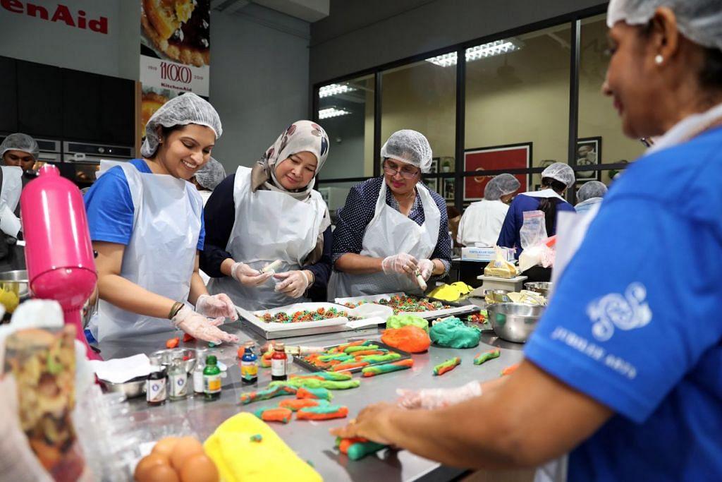 (Dari kiri) Cik Natasha Amin Mohammad, Cik Zainon Haron dan Cik Nazlin Sultananli Jinah membuat kuih untuk diagihkan kepada para penerima sebelum Hari Raya nanti. FOTO: GIN TAY