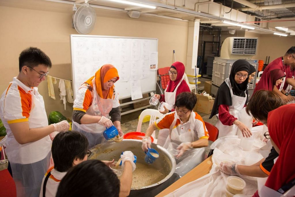SALING KERJASAMA: Sukarelawan Hospital Besar Sengkang sama-sama berkhidmat dengan menyumbang tenaga buat persiapan sebelum mengagih bubur kepada penduduk. – Foto HOSPITAL BESAR SENGKANG