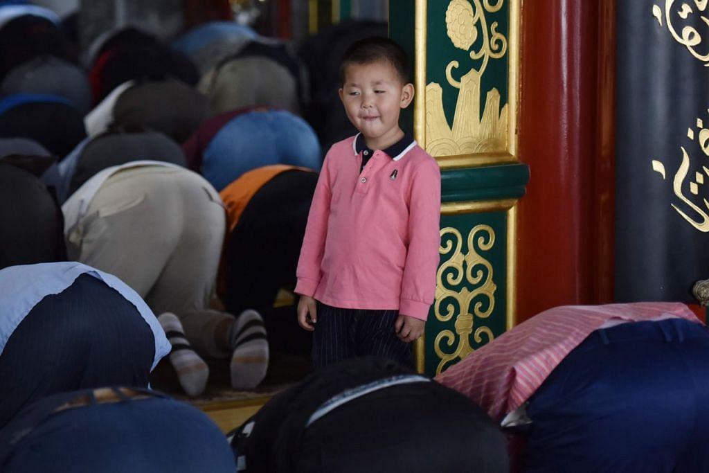 DI CHINA: Seorang kanak-kanak memerhatikan jemaah menjalani solat Jumaat dalam Ramadan di sebuah masjid di Beijing, China. - Foto AFP