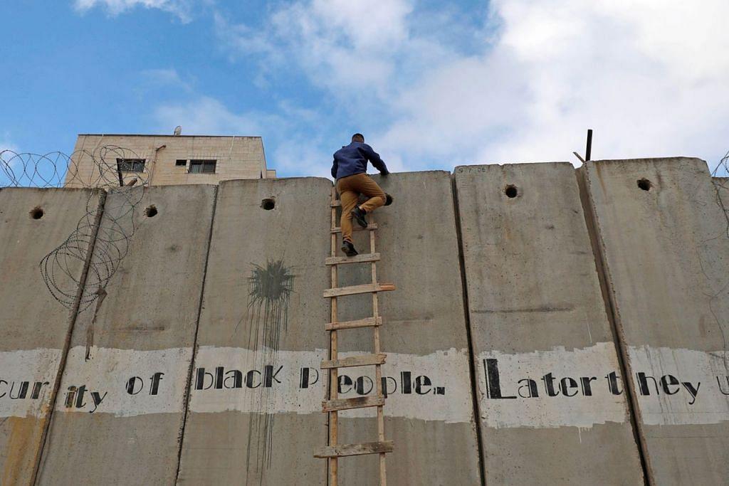 DI PALESTIN: Seorang lelaki Palestin dilihat cuba memanjat tembok yang memisahkan tempatnya dengan Masjid Al Aqsa di Baitulmakdis untuk menunaikan solat Jumaat. - Foto REUTERS