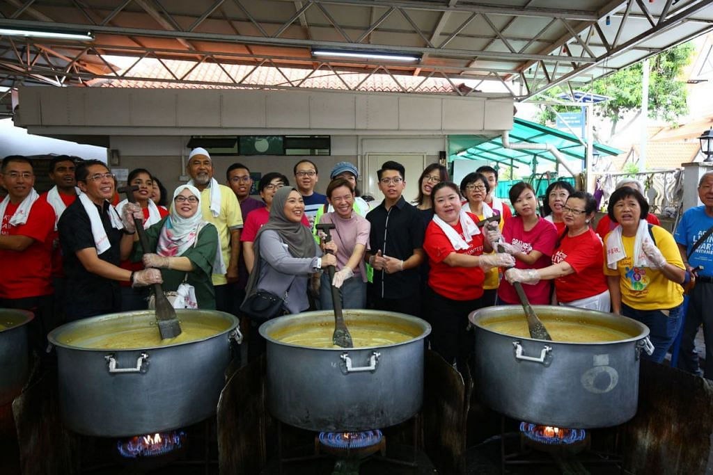 KACAU BUBUR BERSAMA: Dr Maliki (dua dari kiri di barisan depan) bersama isterinya, Cik Sadiah Shahal, serta para sukarelawan, dengan panduan Encik Alla'udin (berkopiah putih), sama-sama menyumbang khidmat menggaul bubur untuk berbuka dan untuk diagih kepada golongan warga emas di sebuah rumah tumpangan kendalian penganut Buddha. - Foto CDC SOUTH EAST