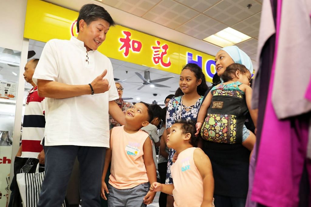 BAWA CERIA: Encik Ng Chee Meng berbual mesra dan turut gembira dengan keluarga ini, yang mendapat baju baru untuk Hari Raya nanti. - Foto BH oleh GIN TAY