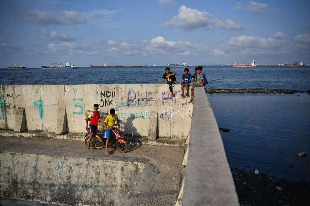 HALANG KE LAUT: Tembok setinggi dua meter membantu menghalang air laut masuk, tetapi menutup akses ke laut bagi penduduk di Muara Baru di Jakarta Utara. - Foto THE STRAITS TIMES