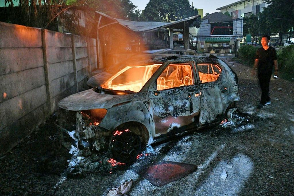 MARAK DENGAN API KEMARAHAN: Penunjuk perasaan membakar kereta di kompleks perumahan Briged Polis Bergerak (Brimob) di Jakarta Barat, Indonesia, kelmarin. - Foto REUTERS