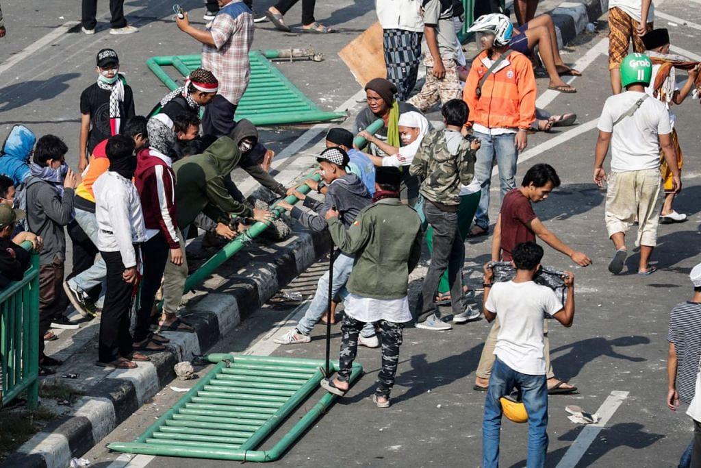 MUSNAHKAN HARTA BENDA AWAM: Perusuh memecah serta menanggalkan besi pembahagi jalan tatkala mereka bertempur dengan pegawai polis. - Foto EPA-EFE