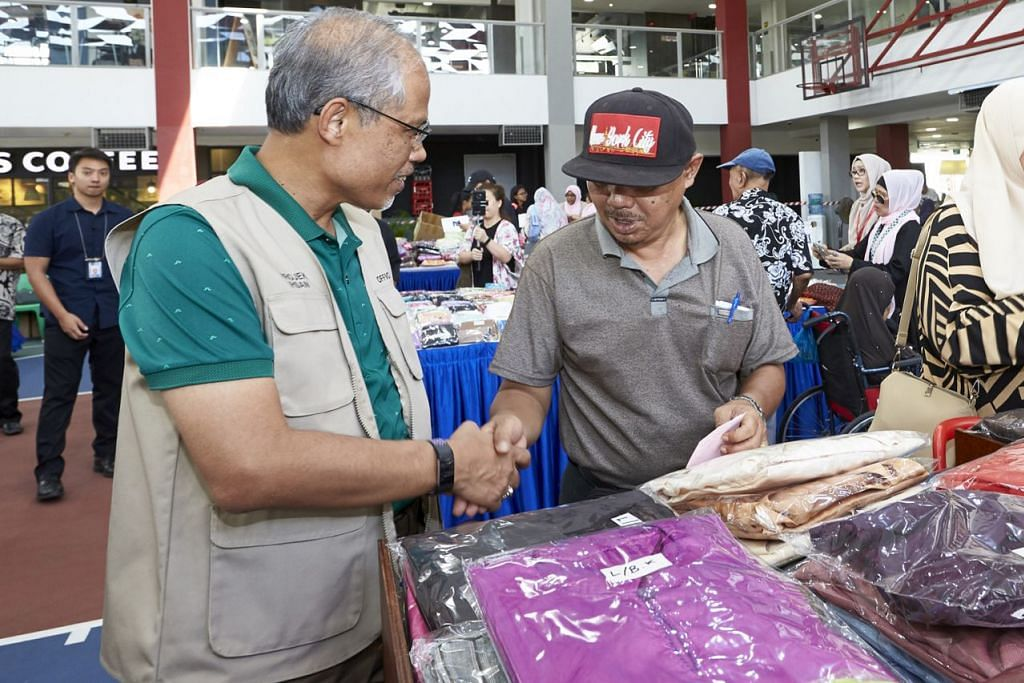 MERIAH LAGI RAYA TAHUN INI: Encik Masagos Zulkifli Masagos Mohamad (kiri) berinteraksi dengan seorang penerima yang tampil memilih pakaian dalam rangka Projek Ihsan 2019 di Kelab Masyarakat Tampines West. – Foto BM oleh ROSLEE RAZAK