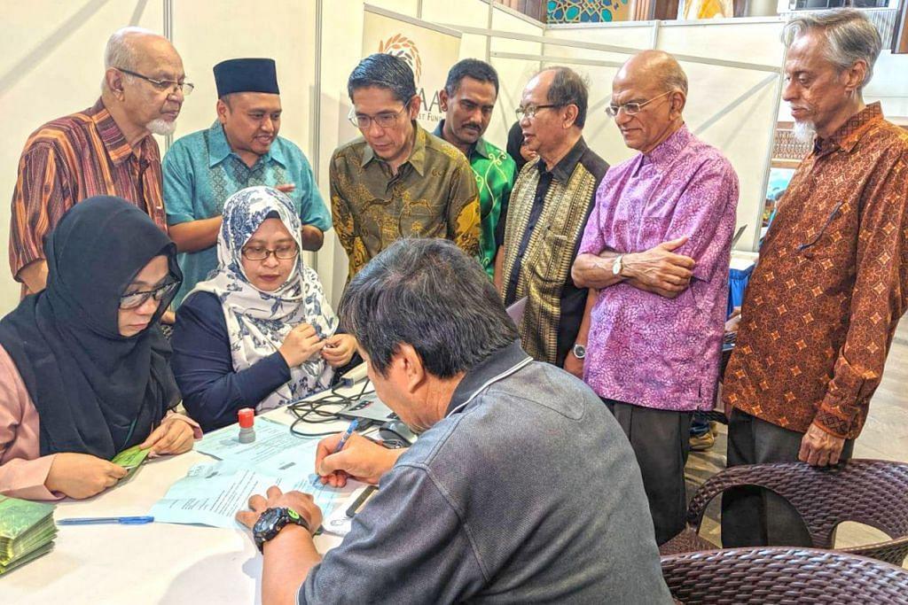 AGIHKAH HABUAN: (Berdiri dari kiri) Pengurus Kanan TAA, Encik Yahya Zakaria; Ketua Jawatankuasa Eksekutif TAA, Encik Harmizan Abdul Hamid; Dr Mohd Maliki Osman, meninjau proses agihan dana TAA kepada penerima. Turut hadir ialah (dari kanan) Presiden Persatuan Persuratan Pemuda Pemudi Melayu (4PM), Encik Izzudin Taherally; dan Presiden Persatuan Bertindak Ginjal Bagi Masyarakat Islam (MKAC), Encik Ameerali Abdeali.  – Foto WGS