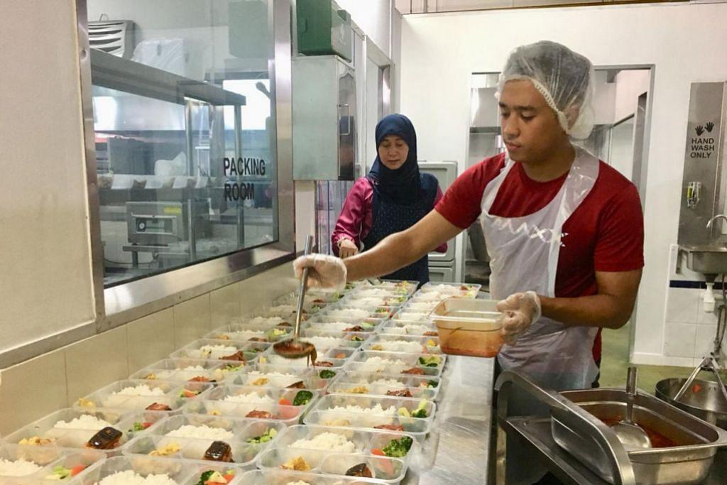MENYIAPKAN MAKANAN 'TINGKAT': Cik Hashimah Nordin dan Encik Muhammad sedang menyediakan makanan 'tingkat' buat penghantaran ke rumah pelanggan oleh Pak Dollah Home Delivery. - Foto MAMANDA FOOD SOLUTIONS
