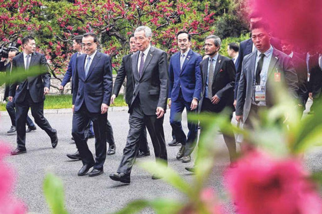 BERAMAH MESRA: Encik Lee (depan, tengah) bersama Perdana Menteri China Li Keqiang berjalan ke tempat menjamu selera bersama rombongan masing-masing di Diaoyu Tai, Beijing, pada 29 April lalu.